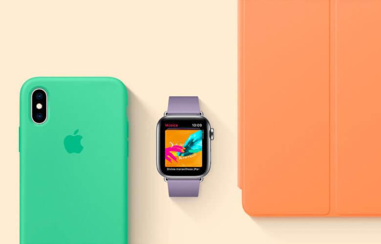 Foto de um iPhone com capa cor hortelã, um Apple Watch com pulseira Lilás e um iPad com capa frontal laranja